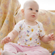 Baby girl sitting on the carpet - Stock Photo