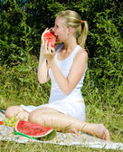 Woman with melon at a picnic — Stock Photo