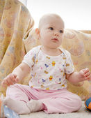 Baby girl sitting on the carpet — Stock Photo