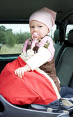 Little girl standing in car seat — Stock Photo