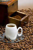 Detail of coffee mill with coffee beans and cup of coffee — Stock Photo