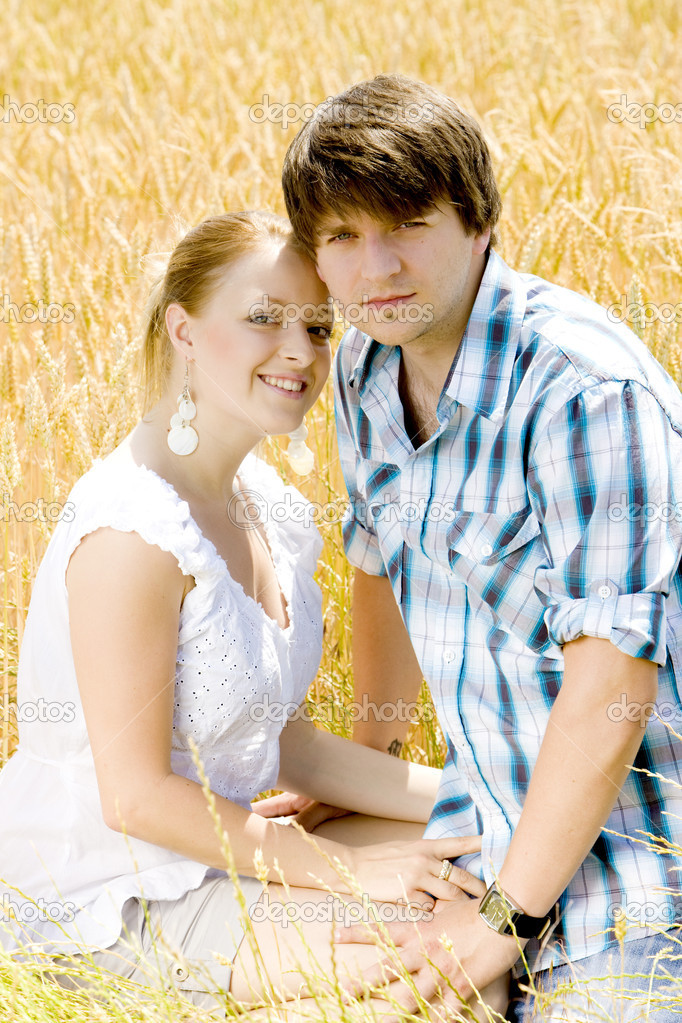 Young couple sitting in grain field  Stock Photo #11283471