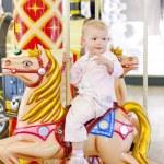 Sitting toddler on carousel — Stock Photo #11290666