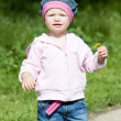 Litlle girl on walk holding a flower — Stock Photo