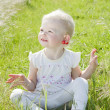 Little girl with cherries sitting on grass — Stock Photo