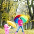 Mother and her daughter with umbrellas in autumnal alley — Stock Photo #11290872