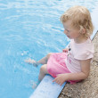 Little girl sitting by swimming pool — Stock Photo #11290941