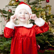 Little girl as Santa Claus by Christmas tree — Stock Photo