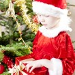 Little girl as Santa Claus with Christmas present — Stock Photo #11291136