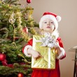 Little girl as Santa Claus with Christmas present — Stock Photo #11291138
