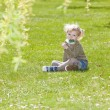 Little girl with a lollipop sitting on grass — Stock Photo