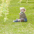 Little girl with a lollipop sitting on grass — Stock Photo #11291173