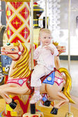 Sitting toddler on carousel — Stock Photo
