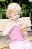 Little girl with ice cream sitting on bench — Stock Photo