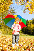 Little girl with umbrella in autumnal nature — Stock Photo