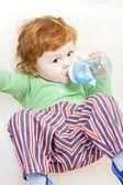 Sitter liten pojke med en botle av vatten — Stockfoto