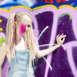 Stock Photo: Portrait of young womstanding at graffitti wall