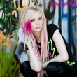 Stock Photo: Portrait of young womsitting at graffitti wall