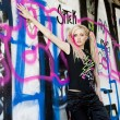 Portrait of young woman standing at graffitti wall — Stock Photo