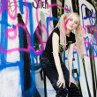 Young woman standing at graffitti wall — Stock Photo