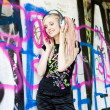 Portrait of young woman with headphones at graffitti wall — Stock Photo