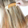 Detail of woman combing long hair — Stock Photo