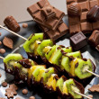 Fruit skewers and chocolate candies — Stock Photo