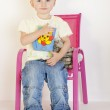 Toddler sitting on chair with toys — Stock Photo #11427735