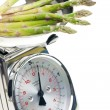 Green asparagus on kitchen scales — Stock Photo #11428011