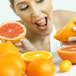 Portrait of young woman with citrus fruit — Stock Photo #11428839