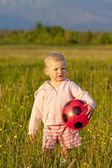 Little girl with a ball standing on meadow — Stock Photo