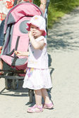 Little girl on walk with a pram — Stock Photo