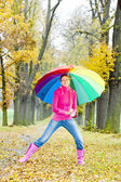 Woman with an umbrella in autumnal alley — Stock Photo