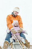 Little girl sledding with mother — Stock Photo