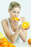 Portrait of young woman eating orange — Stock Photo