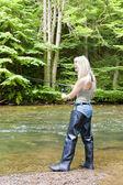 Woman fishing at river — Stock Photo