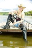 Fishing woman sitting on pier — Stock Photo