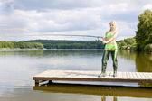 Fishing woman standing on pier — Stock Photo