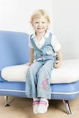 Uma menina sentada no sofá — Fotografia Stock