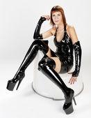 Zittende jonge vrouw extravagante kleren dragen — Stockfoto