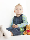 Sitting toddler with a toy — Stockfoto