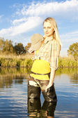 Fisher woman standing in pond — Stock Photo