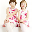 Portrait of two sisters wearing similar dresses - Stock Photo