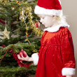 Little girl as Santa Claus by Christmas tree — Foto de Stock