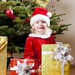 Little girl as Santa Claus with Christmas presents — Stock Photo #11430310