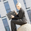Sitting young businesswoman with a briefcase — Stock Photo #11430453