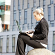 Sitting young businesswoman with a notebook — Stock Photo