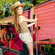 Young woman standing by old threshing machine — Stock Photo #11430521