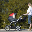 Womwith pushing pram — Stockfoto #11430721