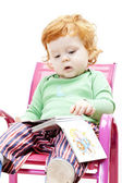 Little boy with a book sitting on chair — Stock Photo